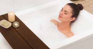 Image of a woman using the Removable Transfer Bench as a shelf while relaxing in a tub